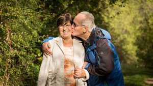 elderly man affectionately kissing woman on cheek